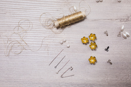 findings: Reel gold thread on a wooden background. Needles and pearls for needlework. Tools for sewing. Fasteners for bra. The process of creativity. seamstress table. Findings .Retro Stock Photo