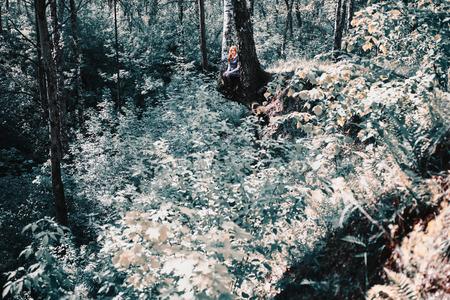 나무에 앉아 파란 드레스에 소녀. 자작 나무 뿌리. 아름 다운 녹색 숲의 배경에 여자. 여름의 푸른 초목입니다.