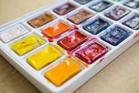 palitra: Solid watercolor tiles in the cold and warm colors on a wooden vintage background. Drawing tools for pupils, students, artists .Palitra of twenty-four colors. Economical and safe material for painting for children Stock Photo