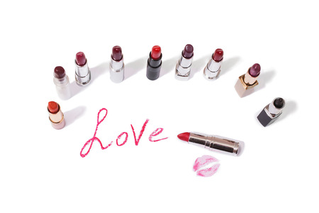 pomatum: Lipstick isolated on white background. Female lip pencil. Kiss of lips on the paper. The word love written in lipstick.