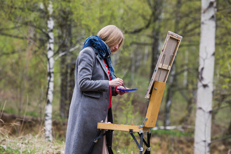 plein: The girl young artist paints a picture in oil on the plein Air . Painting lesson in nature . Blonde draws a self-portrait in the spring forest . Brush on canvas Stock Photo