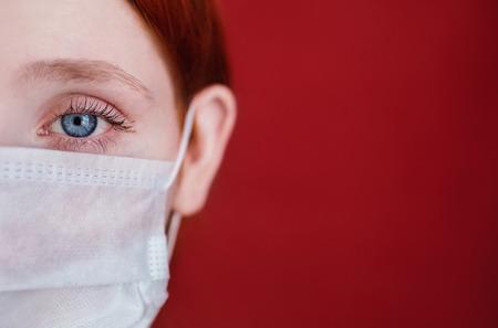 빨간색 배경에 의료 마스크 red-haired 여자, 여자 의사, 강렬한 표정으로 유럽, 절반 얼굴, 머리카락을 고정 스톡 콘텐츠