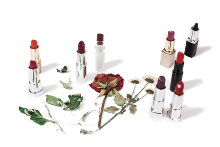 Multicolored glossy lipstick on an isolated background. Herbarium. Dried flowers on a white surface. Dried rose. Cosmetics Lip color