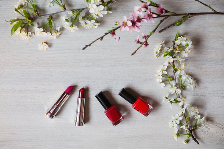 persistent: Lipstick and nail polish purple and red flowers. Tools for creating a flirtatious and attractive image. Persistent cosmetic products for painting. Cosmetics surrounded by white and pink flowers. Stock Photo