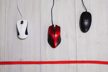 input devices: Interactive race on speed between the red, white and black computer mouse on a wooden gray background. The input device for cursor control. Competition computing devices. Red ribbon Stock Photo
