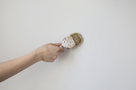 home repairs: Paint brush with a wooden handle in a mans hand on a light background. Home repairs. Concept. The tool for painting of walls. Dirty brush in gray wall. The tool for painting walls