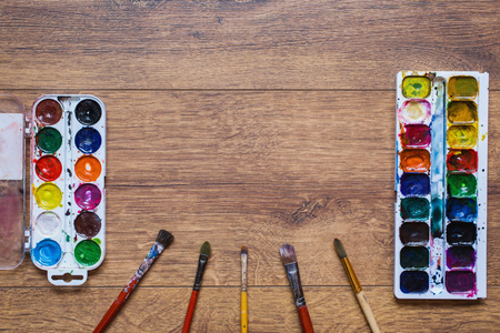 palitra: Artistic squirrel brush and water paints. Drawing tools for pupils, students, artists .Palitra of twenty-four colors. . Economical and safe material for painting with children. Brushes and watercolor on warm wooden background.