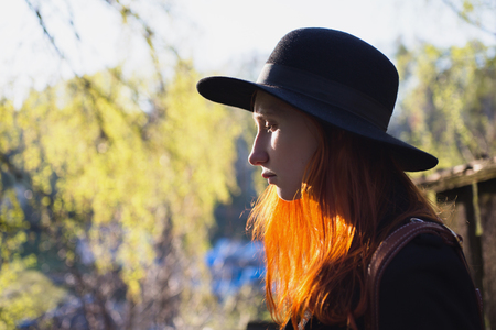 redheaded: Portrait of a redheaded girl with natural light on the background of nature in spring. Woman with hat in backlit.