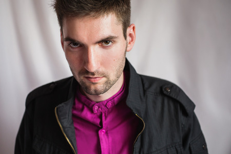 ooking: stylish portrait of a young man in a purple shirt and a black jacket on white background ooking at the camera
