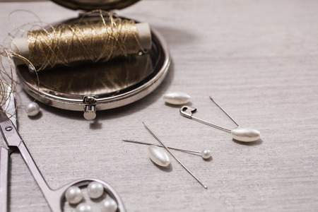 needle laces: Reel gold thread on a wooden table. Pearls, needles, hooks bra Accessories. Tools for needlework. Workplace seamstress. Vintage