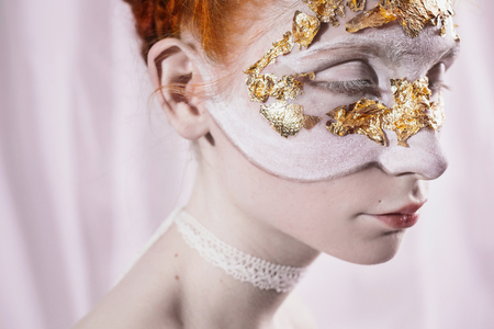 closed ribbon: The girl in a mask of sumalnogo gold with white makeup and white eyelashes on a white background. Pale skin, eyes closed. The ribbon on the neck. Stock Photo