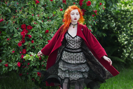 flit: Red-haired girl with pale skin circled in red coat. A woman with a gray dress with tsvetokm on neck on the background of a large bush of red roses. The dress fluttering in the wind. Closed eyes.