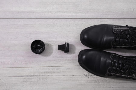 untied: black mens shoes on the wooden background with untied laces, shoe polish