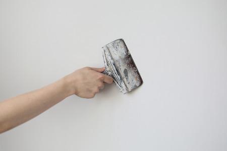 pegamento: herramienta de trabajo, espátula en la mano sobre un fondo claro, escayolista trabajo, pintor, para hacer las reparaciones. Paleta en la mano del hombre sobre un fondo de una pared blanca. Espacio para el texto Foto de archivo