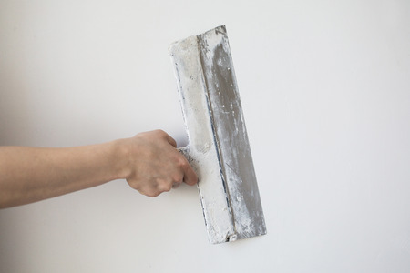 skim: working tool, spatula in hand on a light background, work plasterer, painter, to make repairs