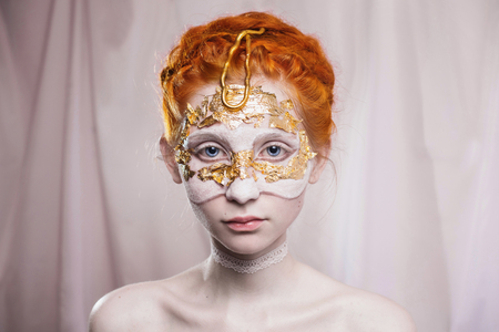 High wedding hairstyle in the Greek style. Vogue style portrait of a girl with a red white and golden bodyart on her face. Body painting project. Woman painted white and gold colors. Insight concept. Makeup Stock Photo