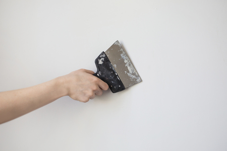 rid: Trowel in mans hand on a background of a white wall. Dirty tools for repair. Tool for getting rid of the wallpaper. Space for text Stock Photo