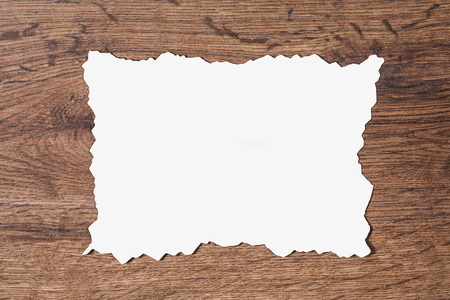 scorched: White sheet of paper scorched by fire on a brown wooden background. Layout.