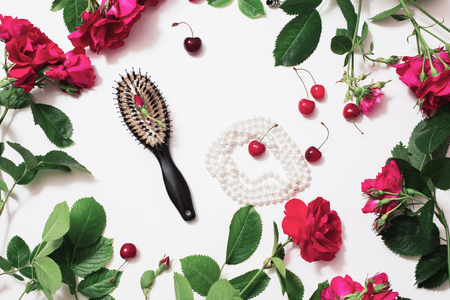 Floral frame of red roses on a white background. Means for the care and beauty. Womens boudoir. Red ripe cherries, black comb, female white beads. Flat lay, top view.