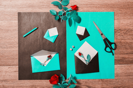 Flower arrangement with stationery items. Lead pencil, scissors, red roses lay on wooden background.