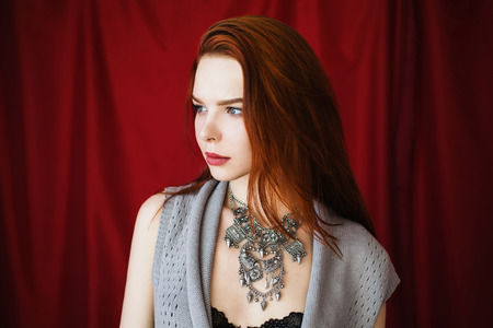 Beautiful red-haired girl with parted lips in black lingerie with necklace around her neck on red background looking away.