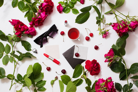 Frame of red beautiful roses with green leaves, lady lipstick, red tea, black glasses, a ring with a black stone, envelope, ripe cherries and a leaf of paper lie on a white background. Flat lay, art Reklamní fotografie