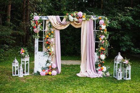 Bella cerimonia di nozze all'aperto. Arco di nozze fatto di stoffa e fiori bianchi e rosa su uno sfondo naturale verde. Vecchie porte, stile rustico. Archivio Fotografico - 71851859
