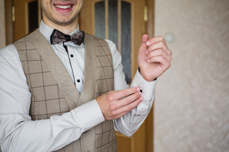 zip tie: Man buttoning on the sleeve of his shirt. Zip up the cufflink. Mens style. Professions. The groom in a bow tie. Going to work, to the meeting. Smile