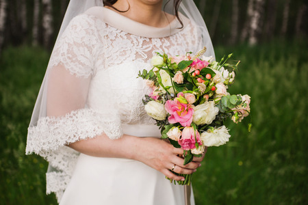 arm bouquet: The bride in a white dress holding a wedding bouquet of white, red and pink colors. White and pink roses. Morning bride Stock Photo