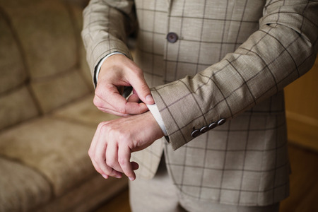A man correct sleeves on the shirt. Mens style. Professions. To prepare for work, Stock Photo