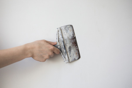 putty knives: working tool, spatula in hand on a light background, work plasterer, painter, to make repairs