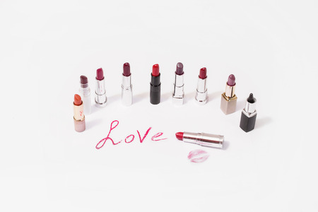 pomatum: Lipstick lie on white background. Female lip pencil. Kiss of lips on paper. The word love written in lipstick. Reflection of lipstick in the mirror. View from above. Concept. Decorative cosmetics Stock Photo