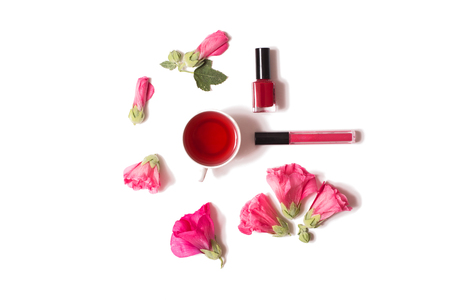 gloss: Red flowers, nail polish, lip gloss are isolated on a white background, flat lay top view.