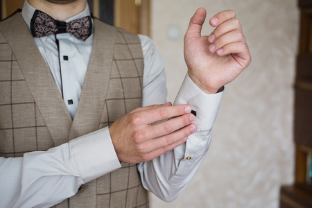 zip tie: Man buttoning on the sleeve of his shirt. Zip up the cufflink. Mens style. Professions. The groom in a bow tie. Going to work, to the meeting. Stock Photo