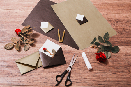 card making: Color paper. Small colored envelopes. Making a greeting card. Workplace designer. Romantic letter. Flower arrangement with stationery items. Red roses with green leaves on wooden background. Flat lay