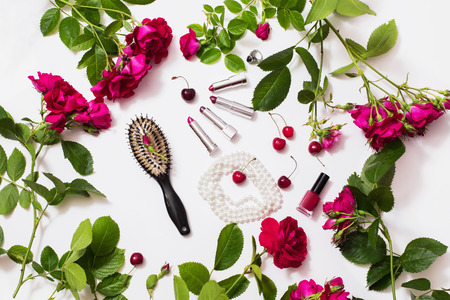 Decorative cosmetics. Make-up. Black comb, red rose buds with green leaves, cherries, female lipstick, nail polish lying on a white background. Frame of flowers. Female boudoir. Flat lay, top view.