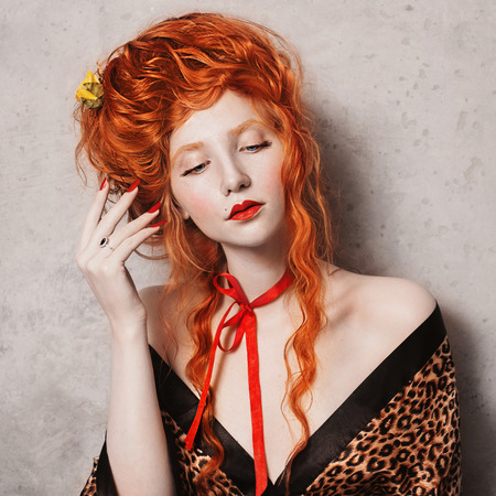 Red-haired girl with red lips in leopard print gown with long hair. Bright unusual appearance