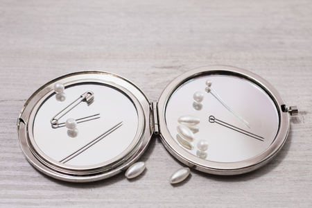Double mirror, pins, needles and sewing items, white beads on a light wooden background