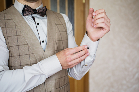 Man buttoning on the sleeve of his shirt. Zip up the cufflink. Mens style. Professions. The groom in a bow tie. Going to work, to the meeting. Stock Photo