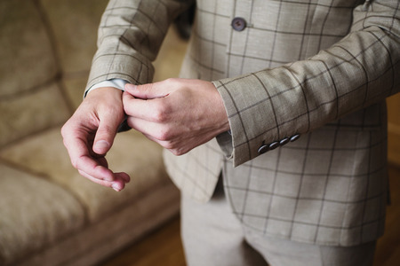 cuff link: A man correct sleeves on the shirt.