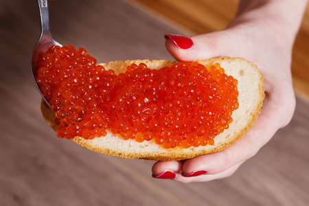 Red caviar close up on a sandwich in a female hand with red nails.