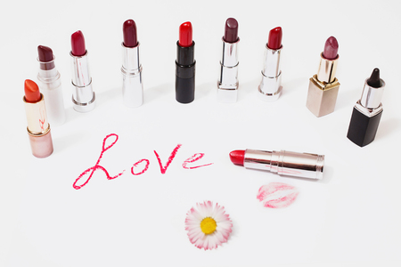 Multicolored glossy lipstick on white background. The word love written in lipstick on a light surface Stock Photo