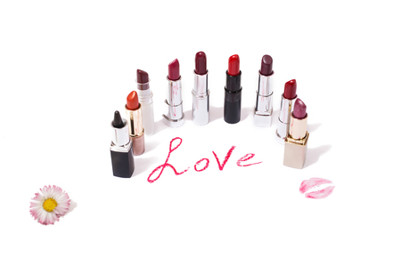 Lipstick isolated on white background. The word love written in lipstick.