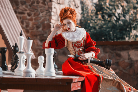 pawn adult: The Red Queen is playing chess. Red-haired woman in a chic vintage dress. Fashion Photo Stock Photo