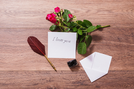 Fountain pen and ink on wooden background. White envelope and red roses. Greeting card. Conceptual photography. Wedding invitation card. Valentine day. Tips to pen. Flat lay, copyspace, mock up