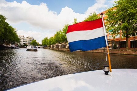 dutch: Dutch flag. Spring sunny Amsterdam. The bright clear blue sky with white clouds. Boat trip on the canals of Amsterdam. The bridge over the water. Travel to Europe