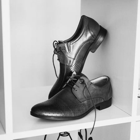 Black and white art photography monochrome, mans shoes stand on a shelf. Mens style, fashion. Charges groom.