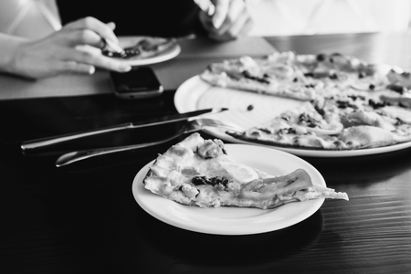 black and white art photography monochrome, a piece pizza with cheese and tomatoes and seafood on a dark background. Girl eating pizza and looking at smart phone. Pizza is on the plate.