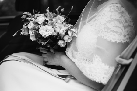 black and white art photography monochrome, bride in a white dress holding a wedding bouquet. White roses. Morning bride