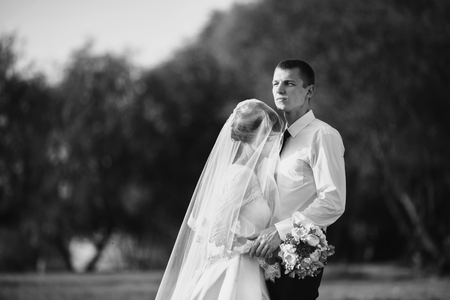 Black and white art photography monochrome, wedding couple on nature with sunlight. Love between a man and a woman. Bride in wedding dress. The groom in a suit. Beautiful wedding bouquet